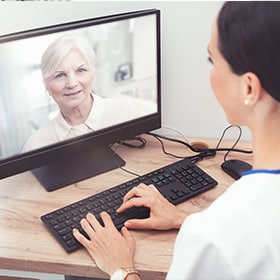Woman on computer using telehealth